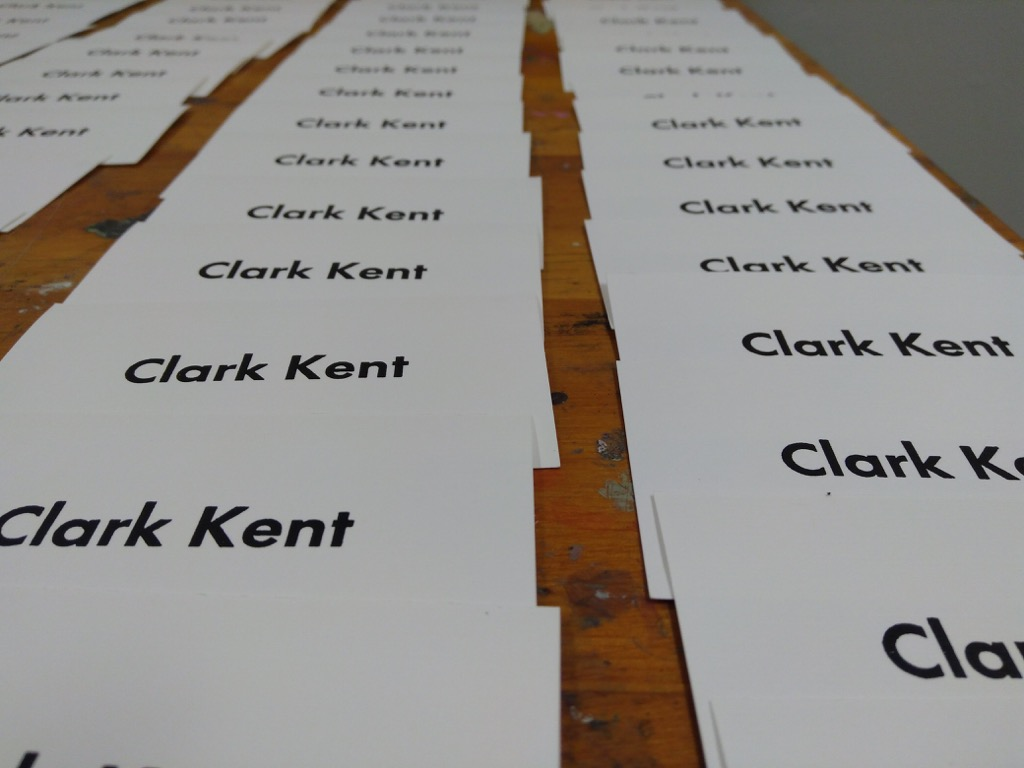 Photo of a collection of freshly-printed Clark Kent business cards,