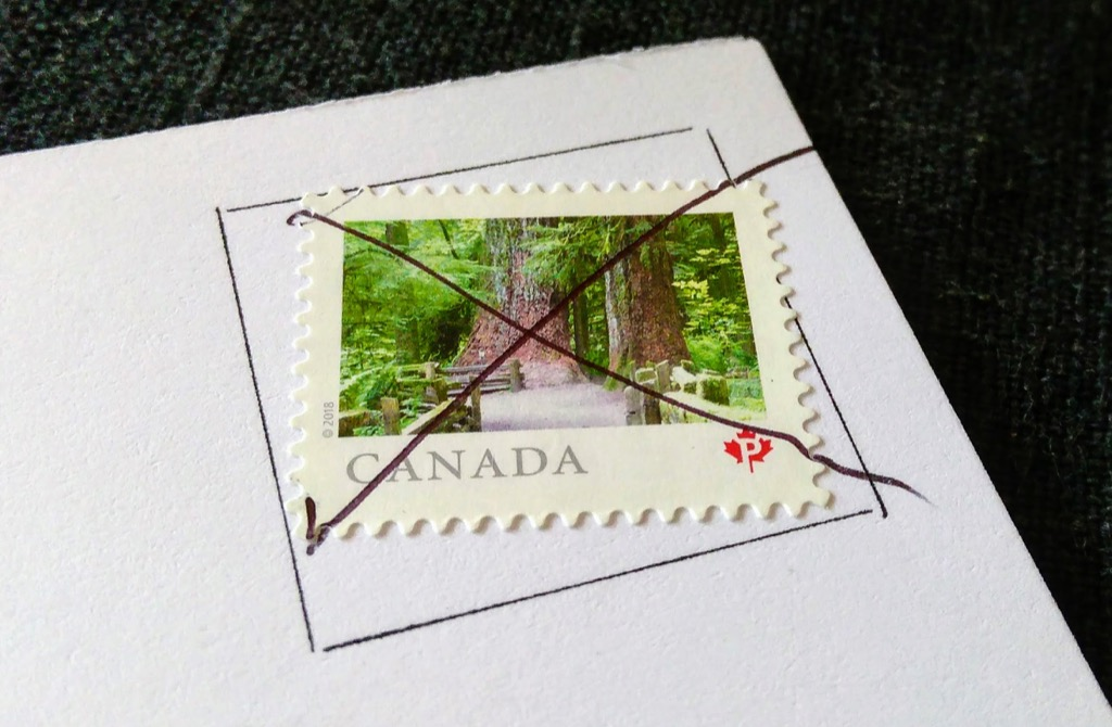 Detail of a postcard stamp cancelled with a pen stroke by Canada Post.