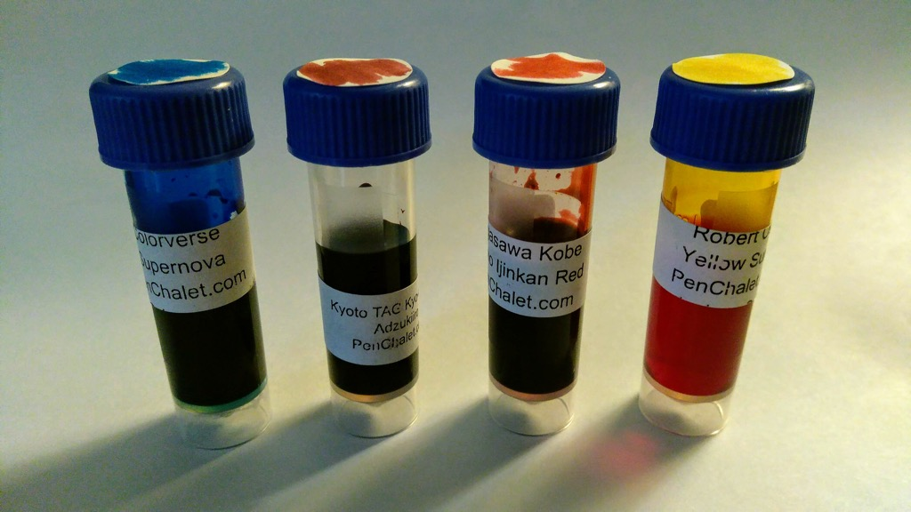 Photo of sample bottles of four colourful fountain pen inks.