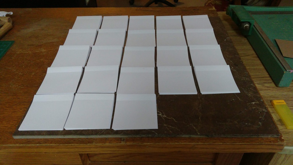 23 sets of perforated signatures ready for binding.