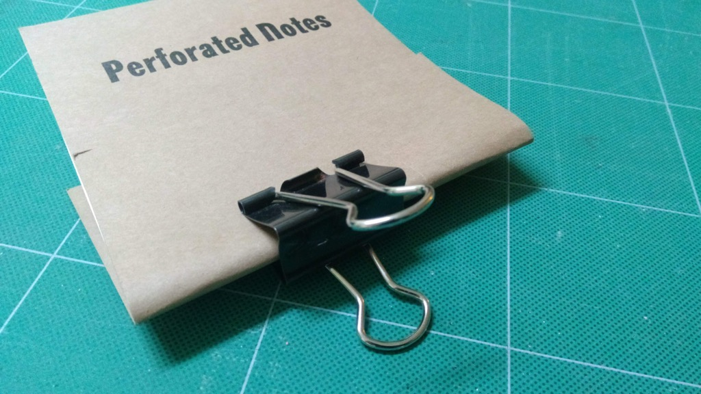 Photo of the binder clamp holding the notebook raw materials together.