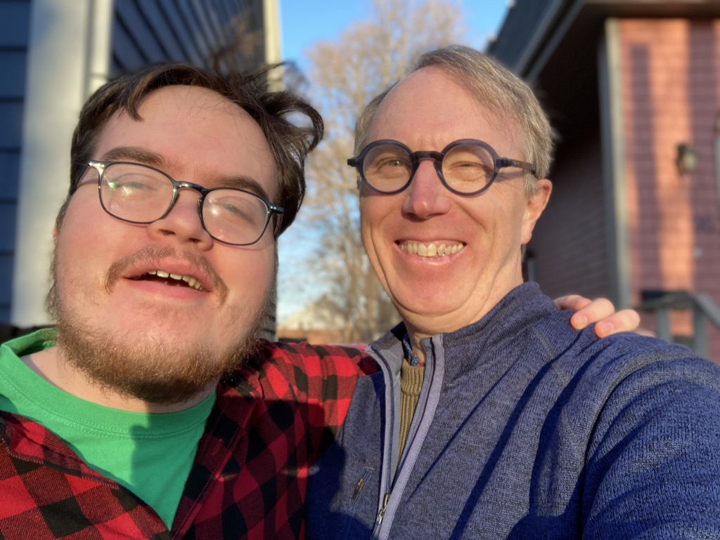 Photo of me and Oliver in the Christmas Eve sun, in front of our house.