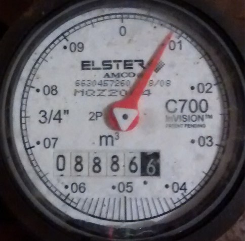 Analog water meter showing 8886.6 reading.