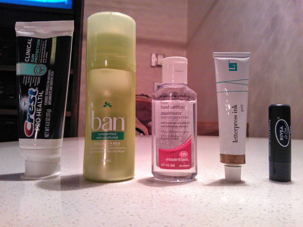 Photo of 5 liquids and gels: toothpaste, deodorant, hand sanitizer, printing ink, lip balm.