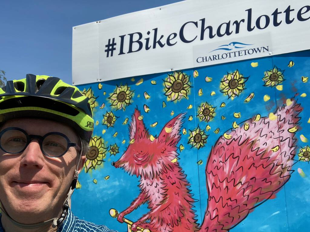 Photo of me, on my bike, in front of the #IBikeCharlottetown billboard on the Confederation Trail near the Farmers' Market