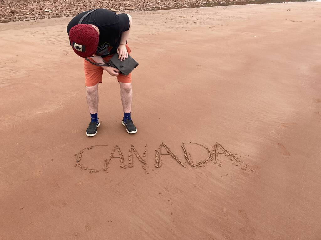 Oliver on the beach, with Canada written in the sand.