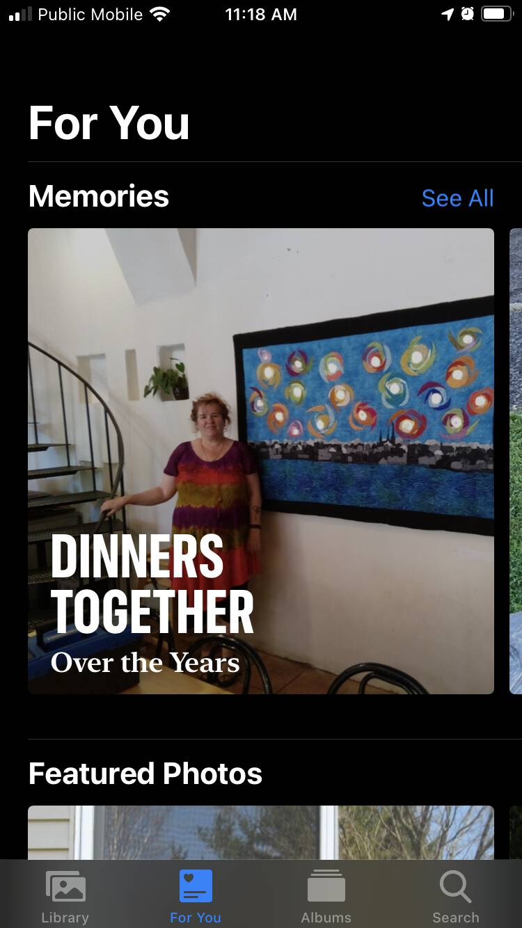 "Screen shot of the For You section of the Photos app on my iPhone, showing a photo of Catherine in front of her artwork, with bold headline ""Dinners Together: Over the Years"" superimposed."
