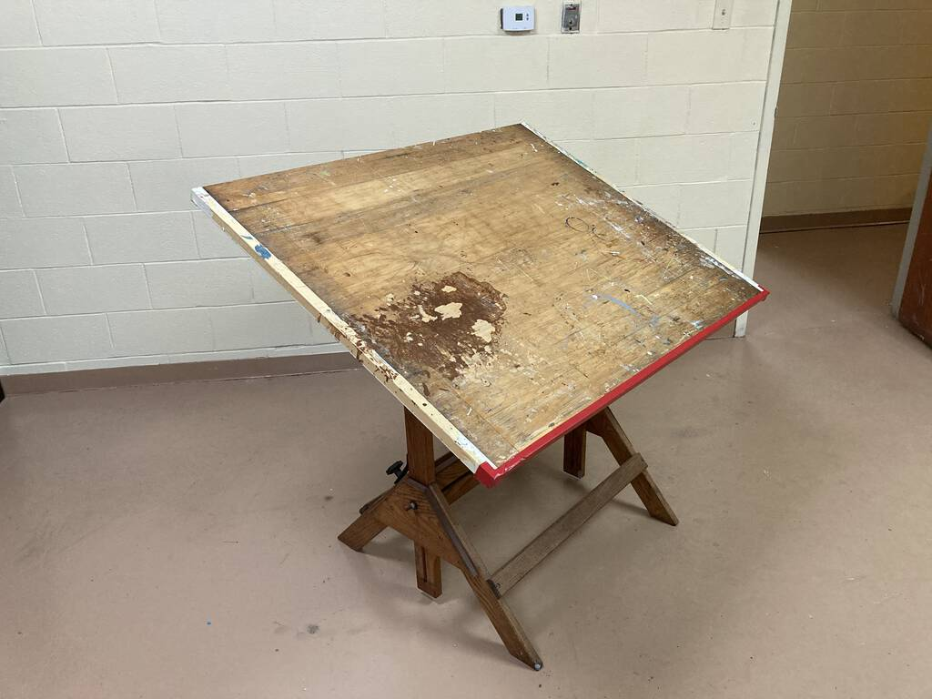 Photo of a wooden drafting table, tilted 45 degrees, on a concrete floor.