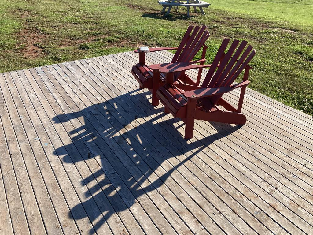 Two red Adirondack chairs at East Point, set on a wood platform overlooking the sea.