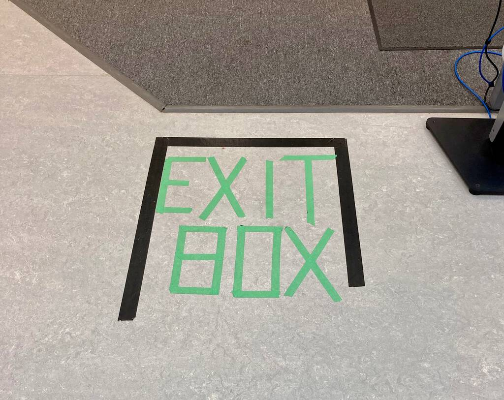 "Photo of ""Exit Box"" sign on the floor, in painter's tape, at Canadian Blood Services."