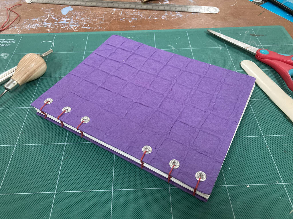 Photo of a coptic-stitched book with a textured purple cover and red stitching, sitting on a green cutting mat.
