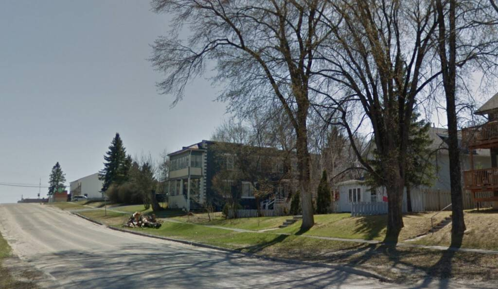 Photo from Google Street View up 5th Avenue in Cochrane, Ontario, showing a rectangular concrete-block building in the distance.