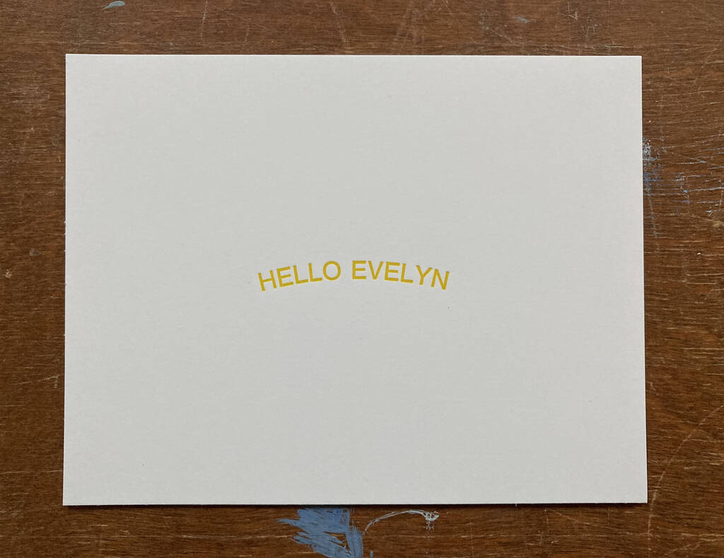 HELLO EVELYN printed in yellow on white card stock, sitting atop a wooden table.