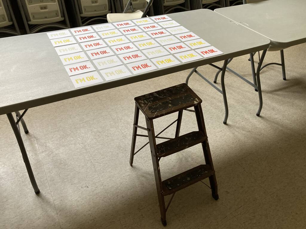 "A set of ""I'm OK"" cards laid out, in different colours, on a table."