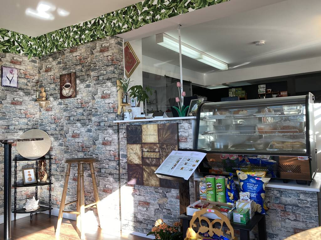 Inside the restaurant, showing cash area, refrigerated case, and decor, which features faux grey brick wallpaper trimmed with faux green leaf border.