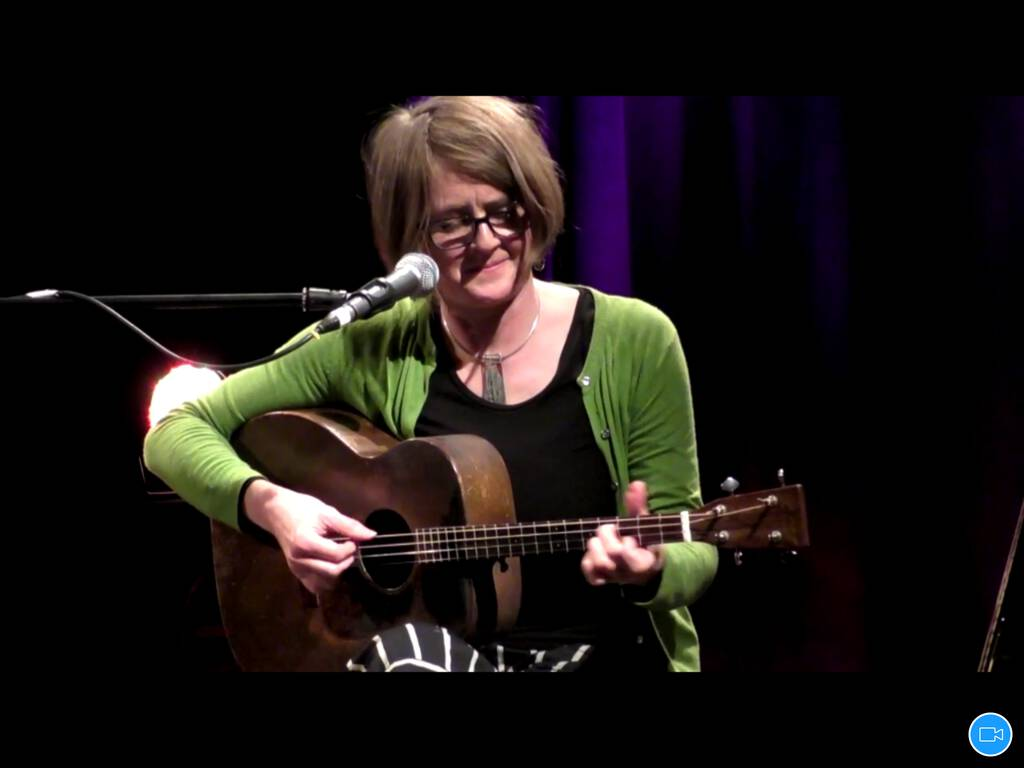 Screen shot of Karine Polwart on Zoom, playing guitar.