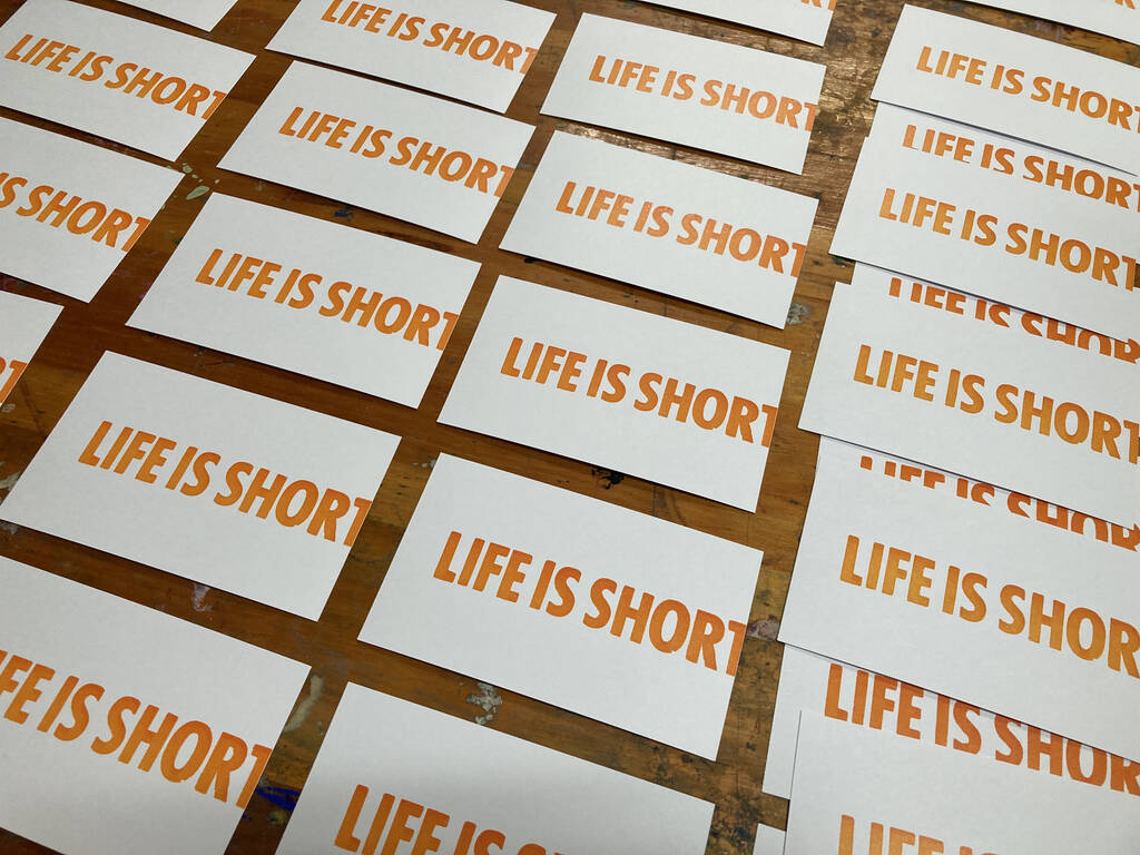 Many Life is Short cards sitting out to try on a wooden table.