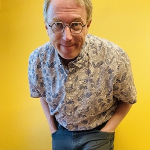 A picture of Peter Rukavina leaning forward against a yellow background. He is a white man in his 50s with short greying hair, wearing a flowered shirt and orange eyeglasses.