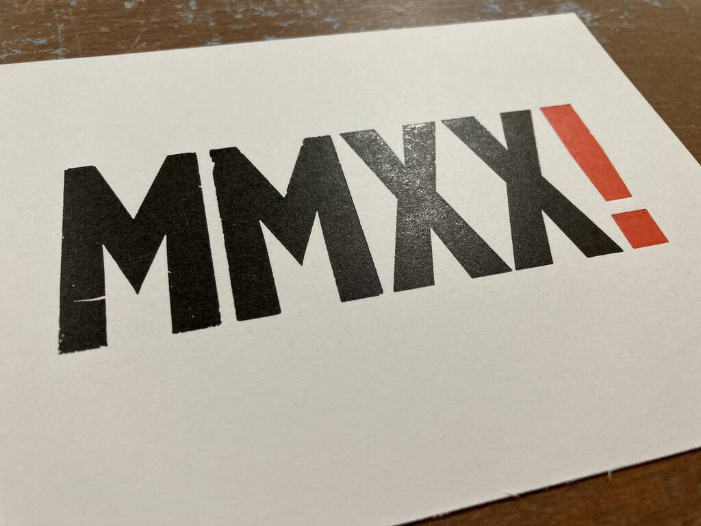 Freshly printed card with MMXX in black and exclamation mark in red.