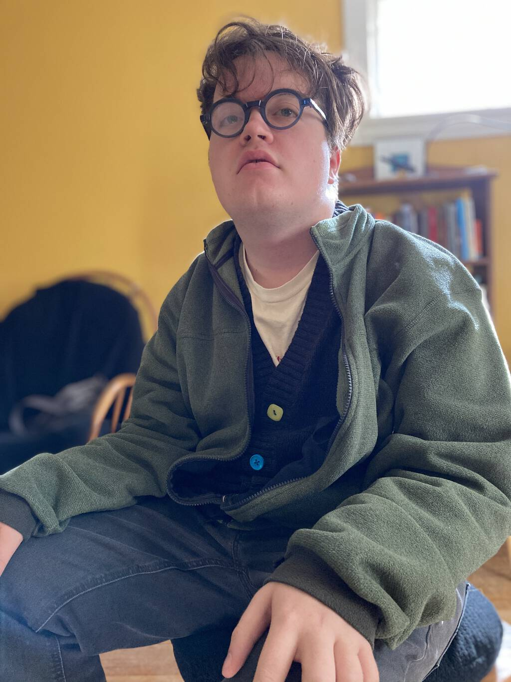 Photo of Oliver sitting in the living room, dressed as Peter, in a cardigan, and wearing my round, blue eyeglasses.