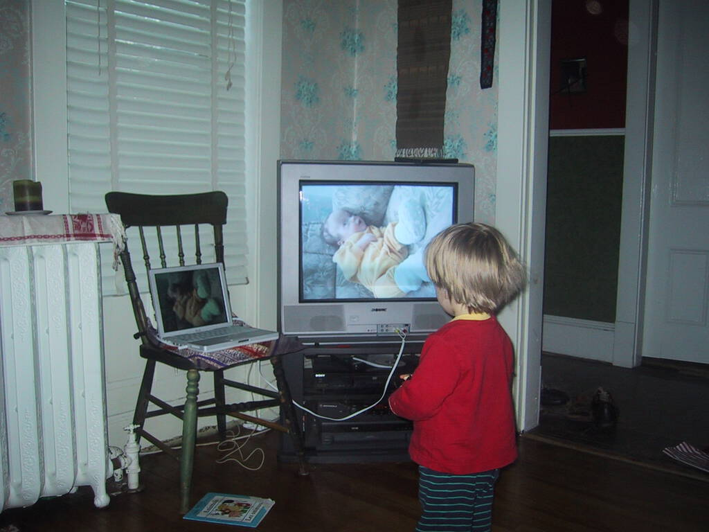 Photo of Oliver looking at a photo of Oliver on the television.