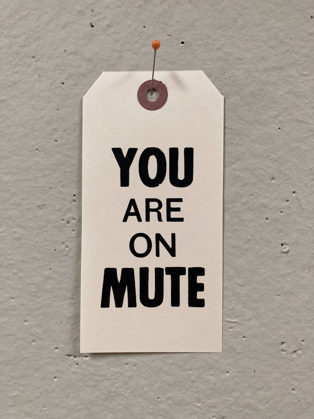 You Are On Mute, printed on a number 6 shipping tag in black ink, hanging on a bulletin board.