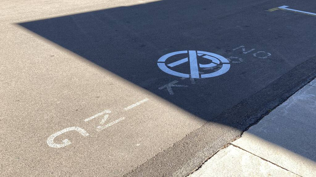 Photo of No Parking zone, showing P with circle and slash painted over the words No Parking from previous years.