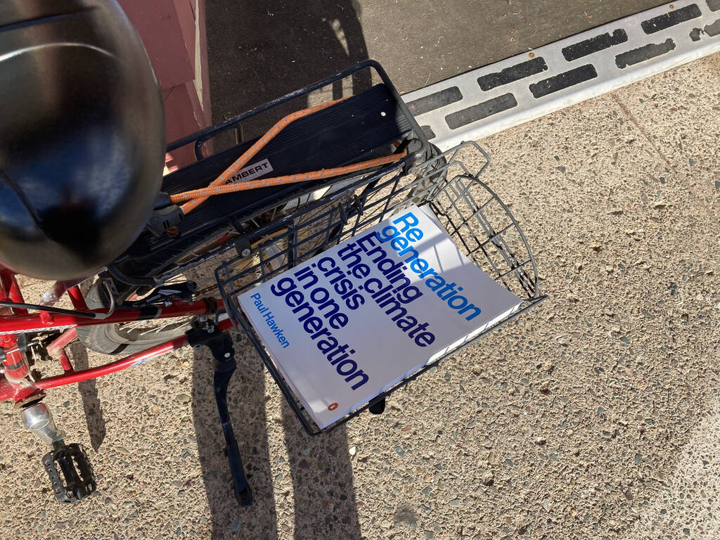 A copy of the paperback book by Paul Hawken, Regeneration, in my bicycle carrier.
