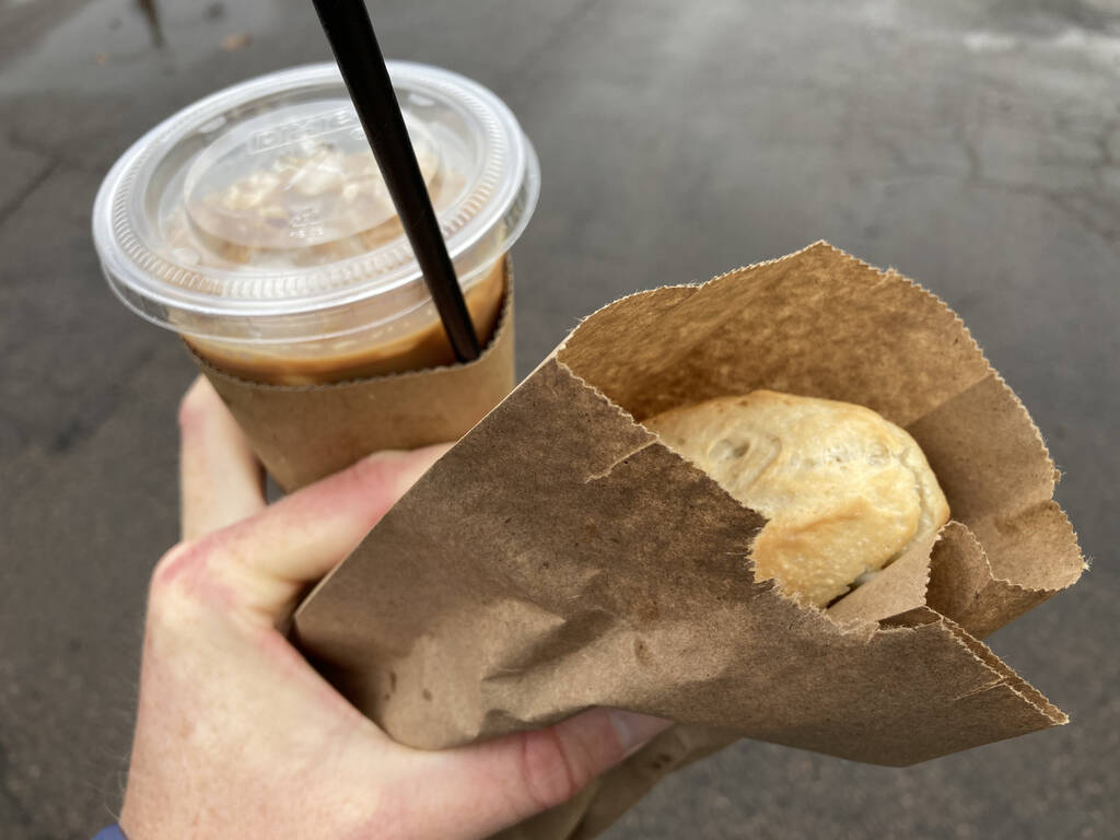 Photo of my left hand holding a plastic cup, with cover and straw, holding brown iced coffee, and showing the tip of a sandwich in a paper bag.
