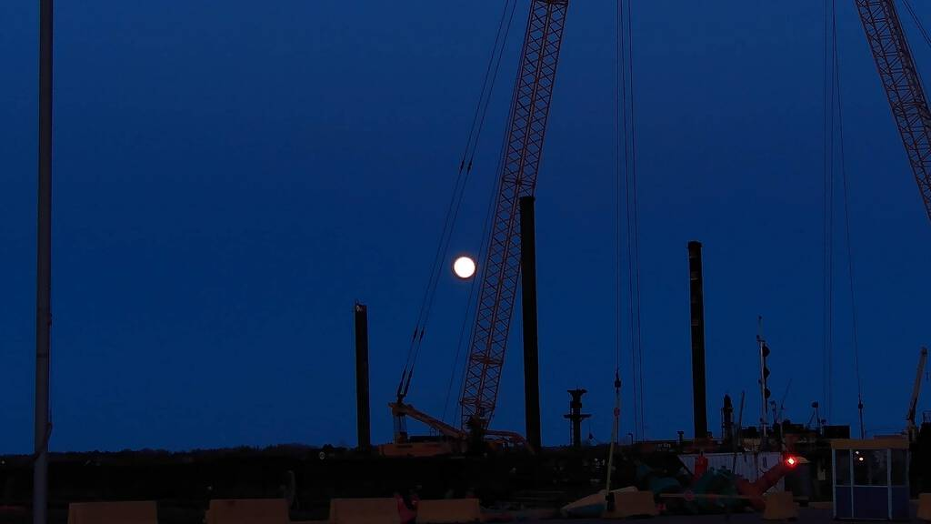 Photo of the Pink Moon behind a crane at Charlottetown waterfront.