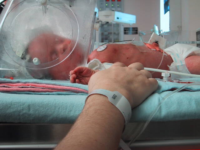 Catherine holding Olivia's hands in the NICU.